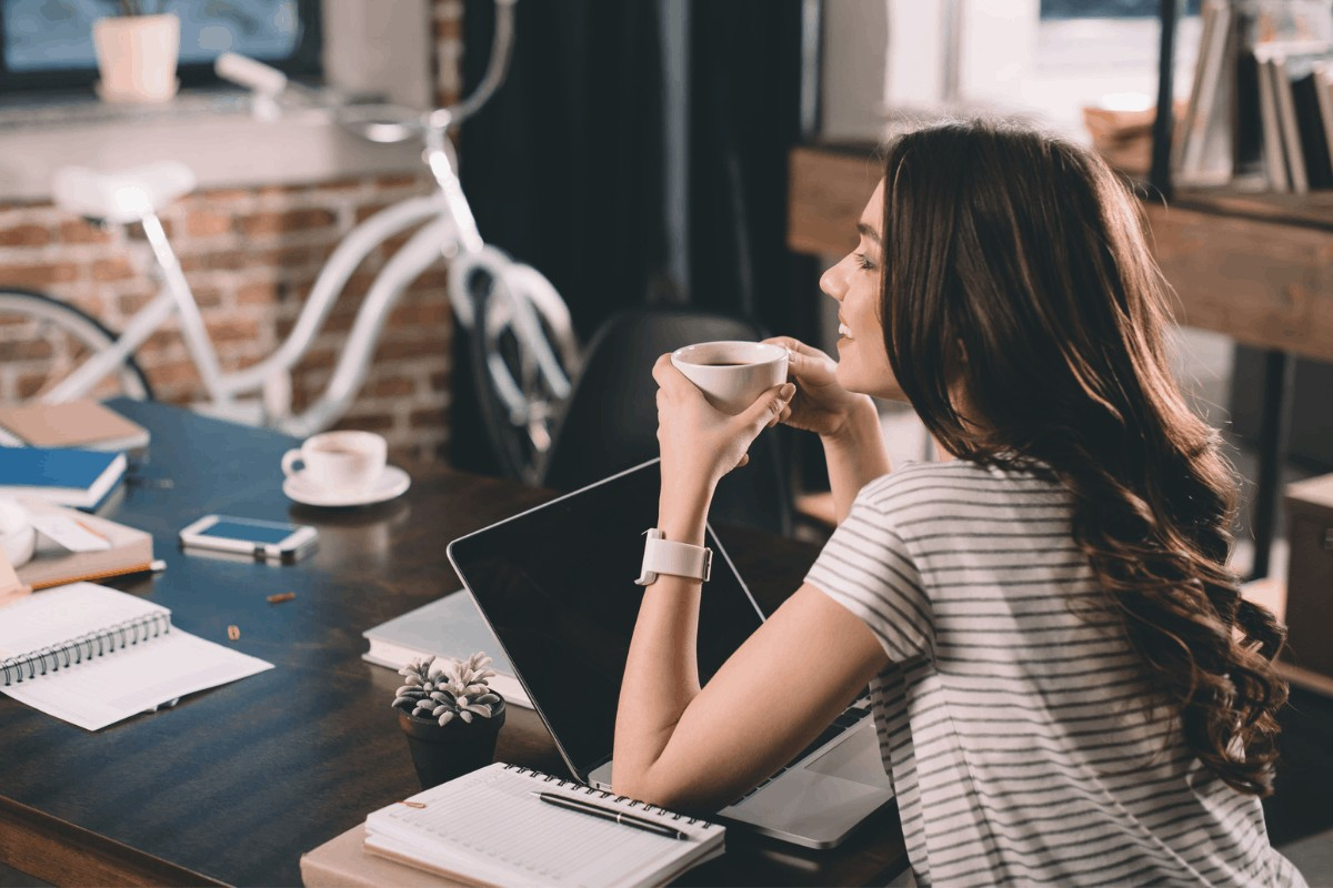 a woman drinking coffee and working on a computer