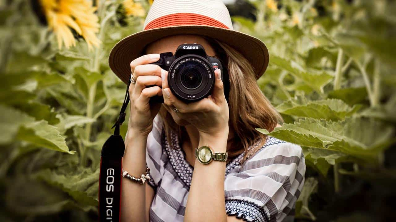 a photo of a woman pointing a camera at the camera with green trees behind
