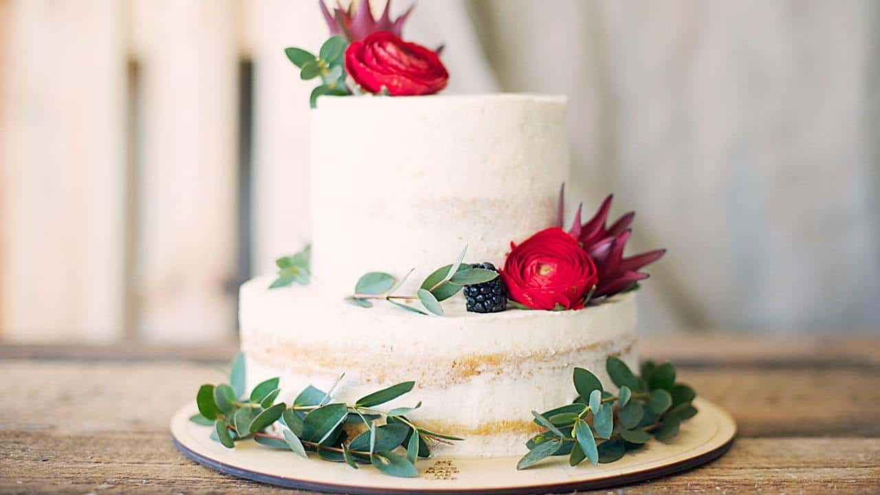 a white cake with multiple tiers decorated with green leaves and pink flowers
