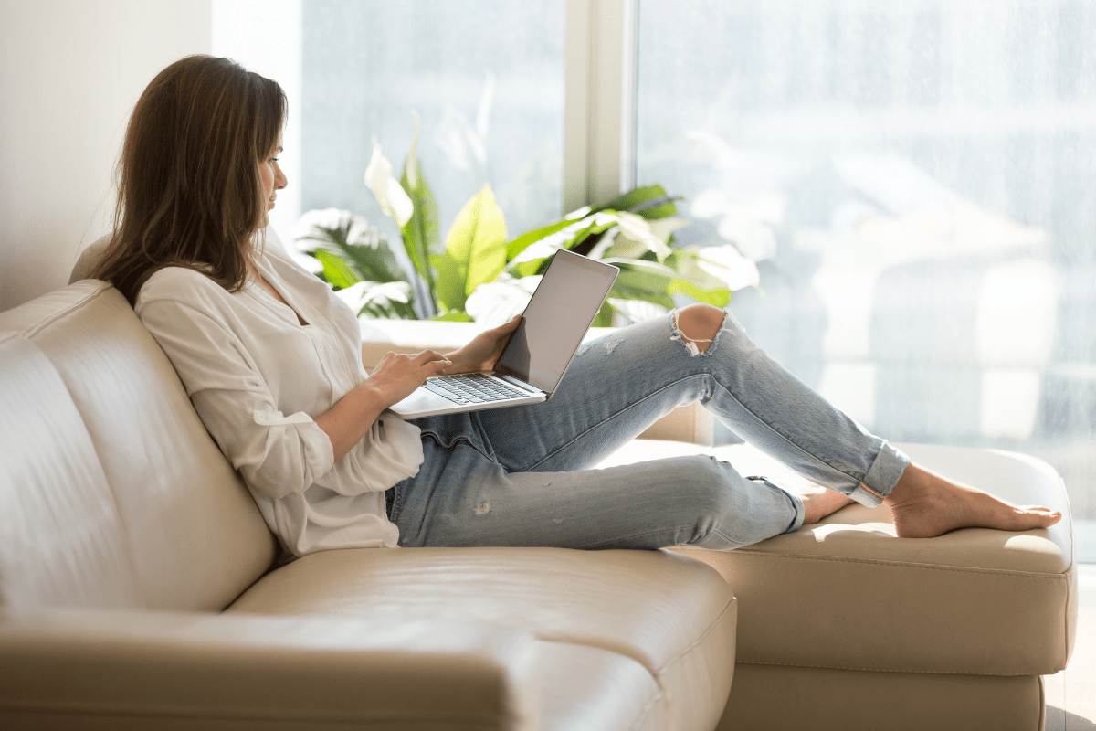 picture of woman sitting on couch searching the web