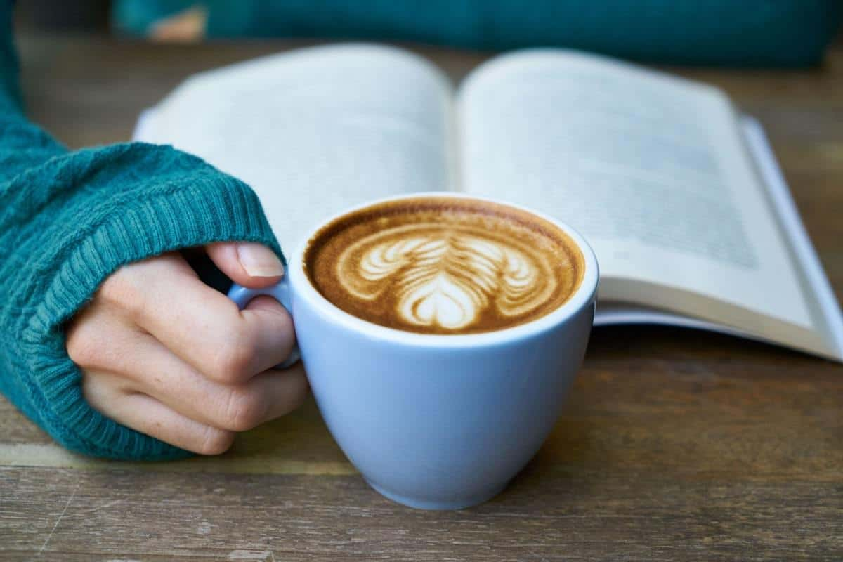 proofreader holding book and drinking coffee