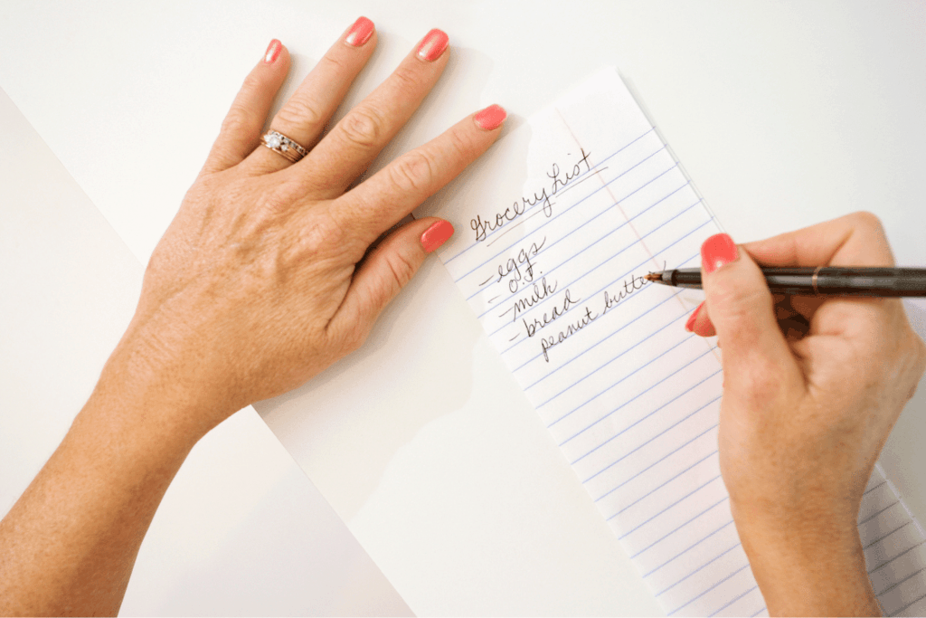 Woman writing grocery list save money by meal planning