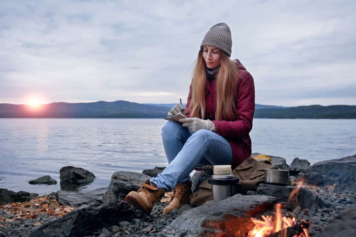 a woman sitting on rocks by the water writing in front of a fire
