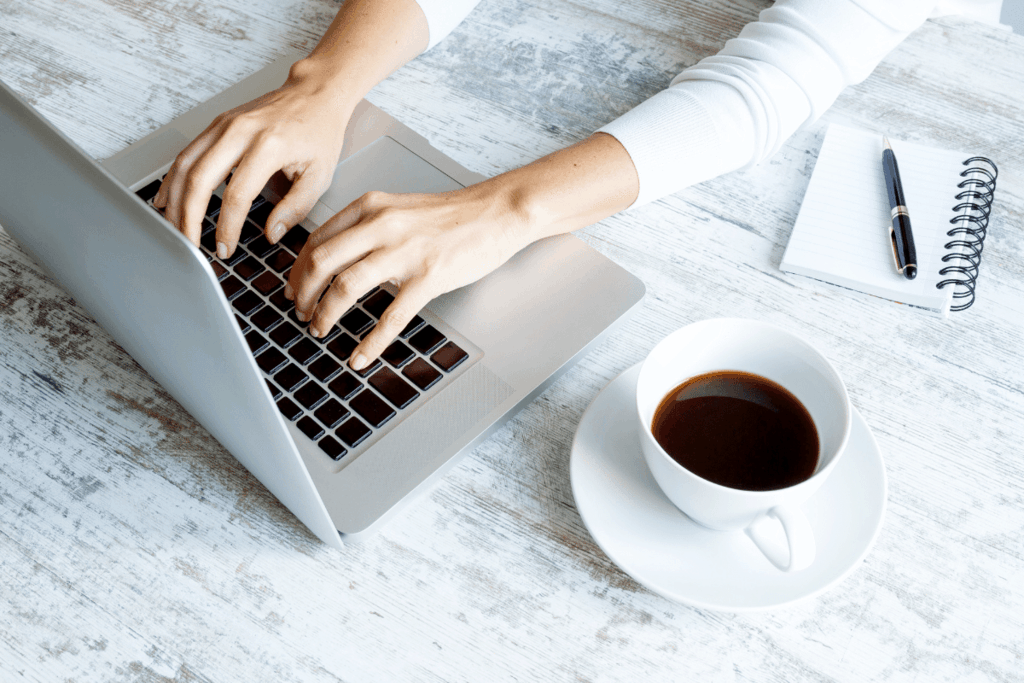 woman typing on macbook with cup of coffee next to her