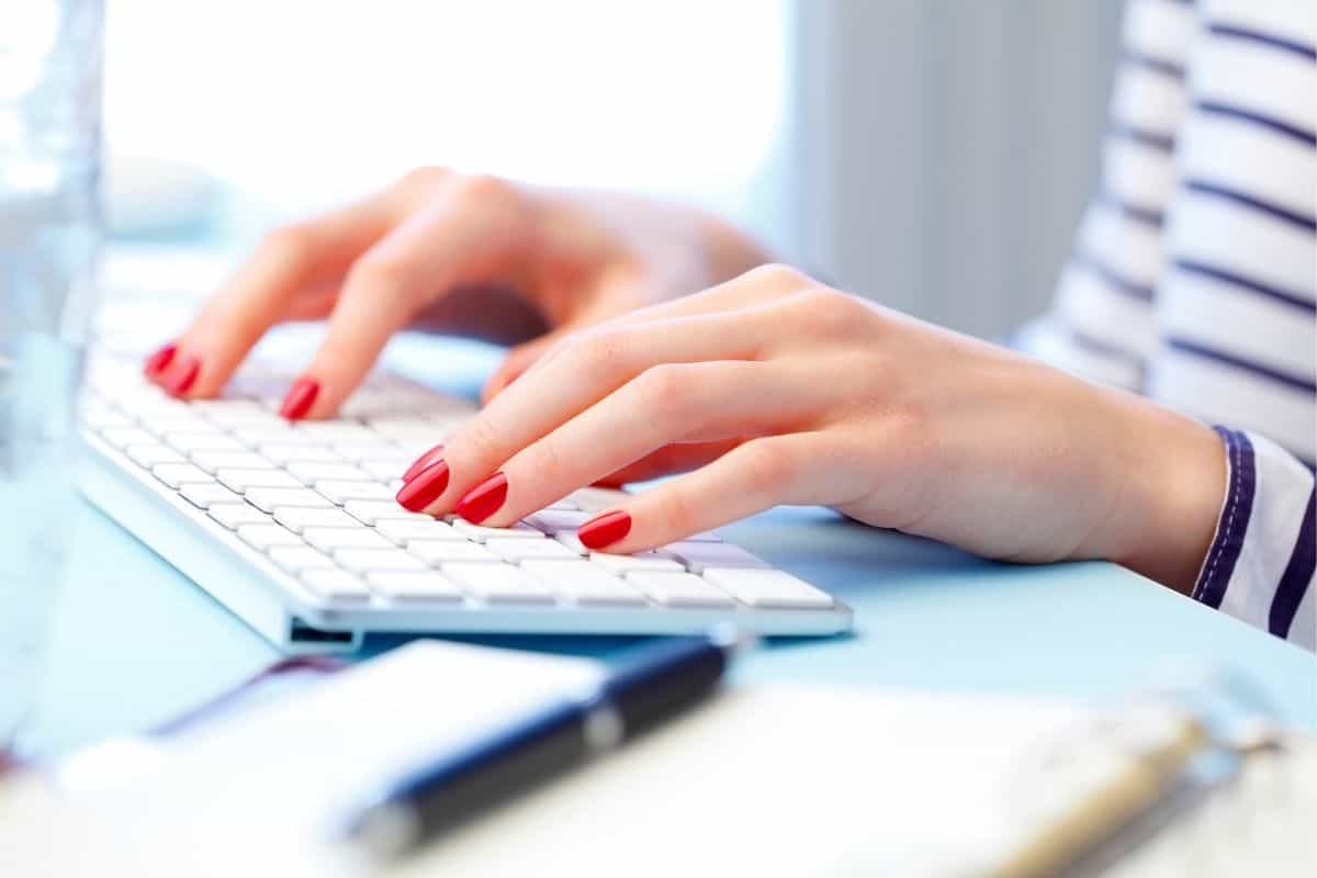 woman typing on laptop computer working from home