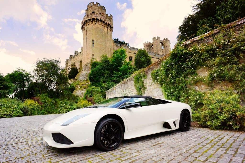 white lamborghini parked in front of castle