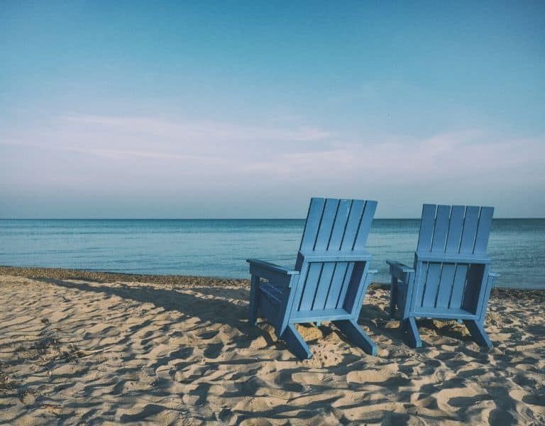 photo of a beach with two blue beach chairs on the sand