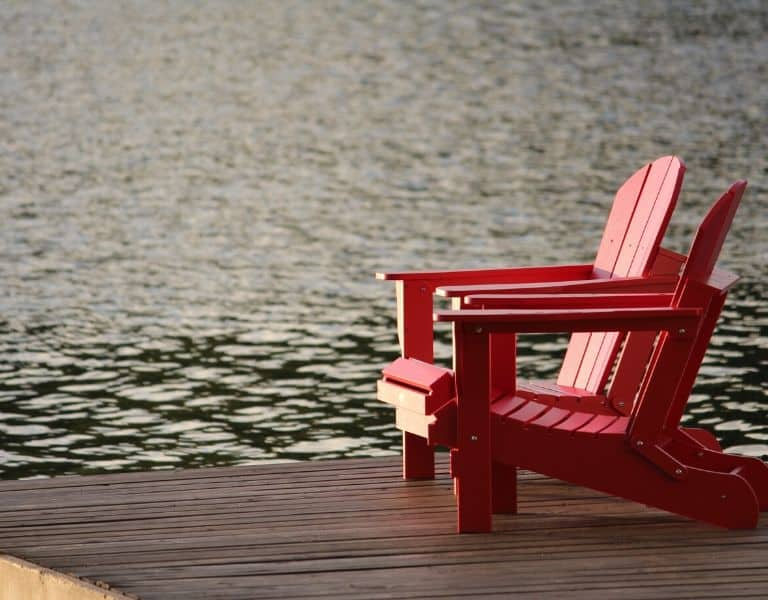 2 red chairs on a dock over water