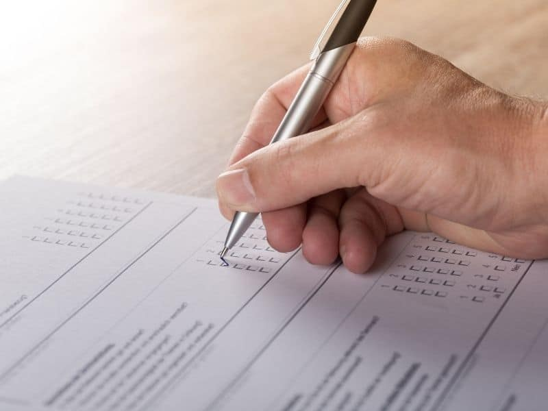 a hand holding a pen filling out a survey