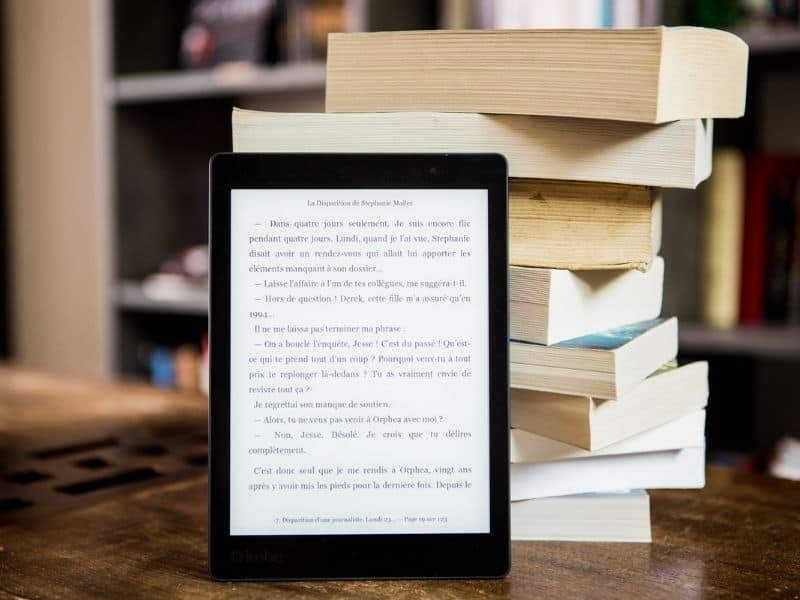 kindle leaning up against a stack of books