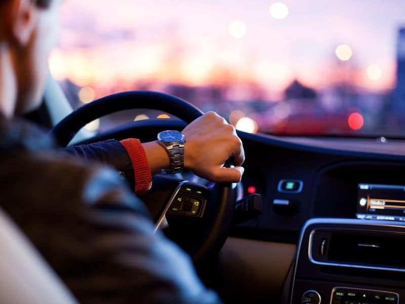 a person driving with hand on the steering wheel