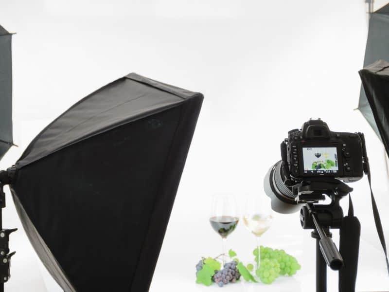 camera on a tripod facing towards 2 wine glasses