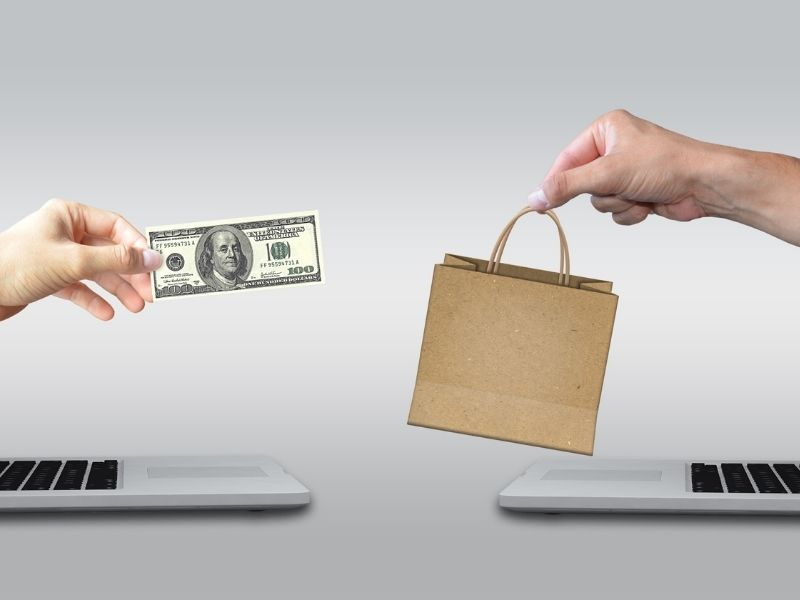 hands coming out of computer screens to exchange a paper bag for money