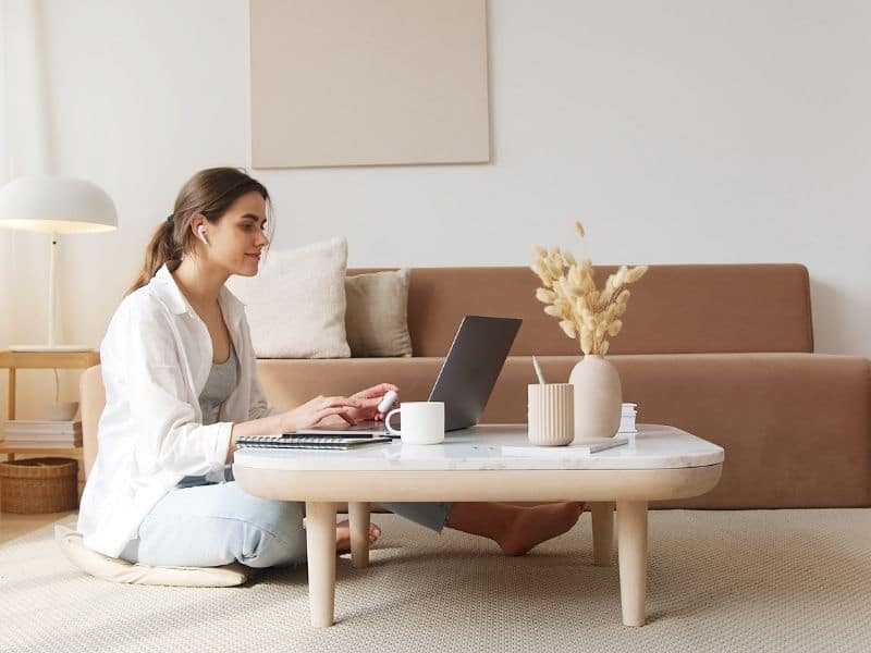 a woman sitting at a coffee table typing on a laptop