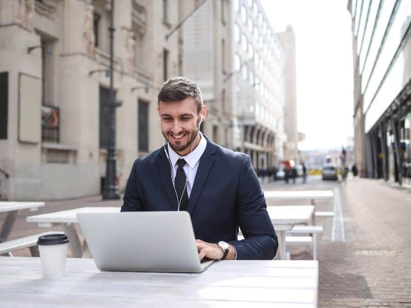 a man in a suit working on a laptop outside