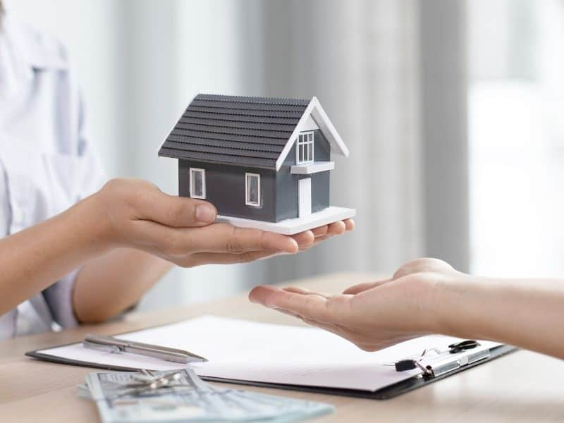 a pair of hands holding a model home over a desk with paperwork on it