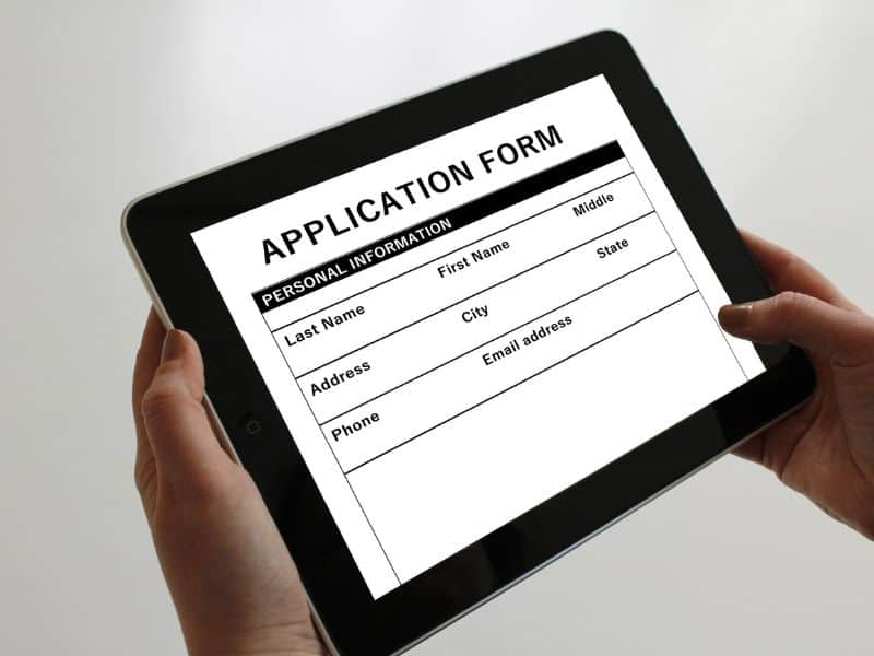 hands holding a tablet with application form on the screen