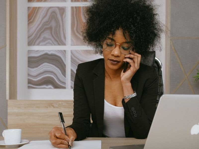 a woman on the phone writing on a desk