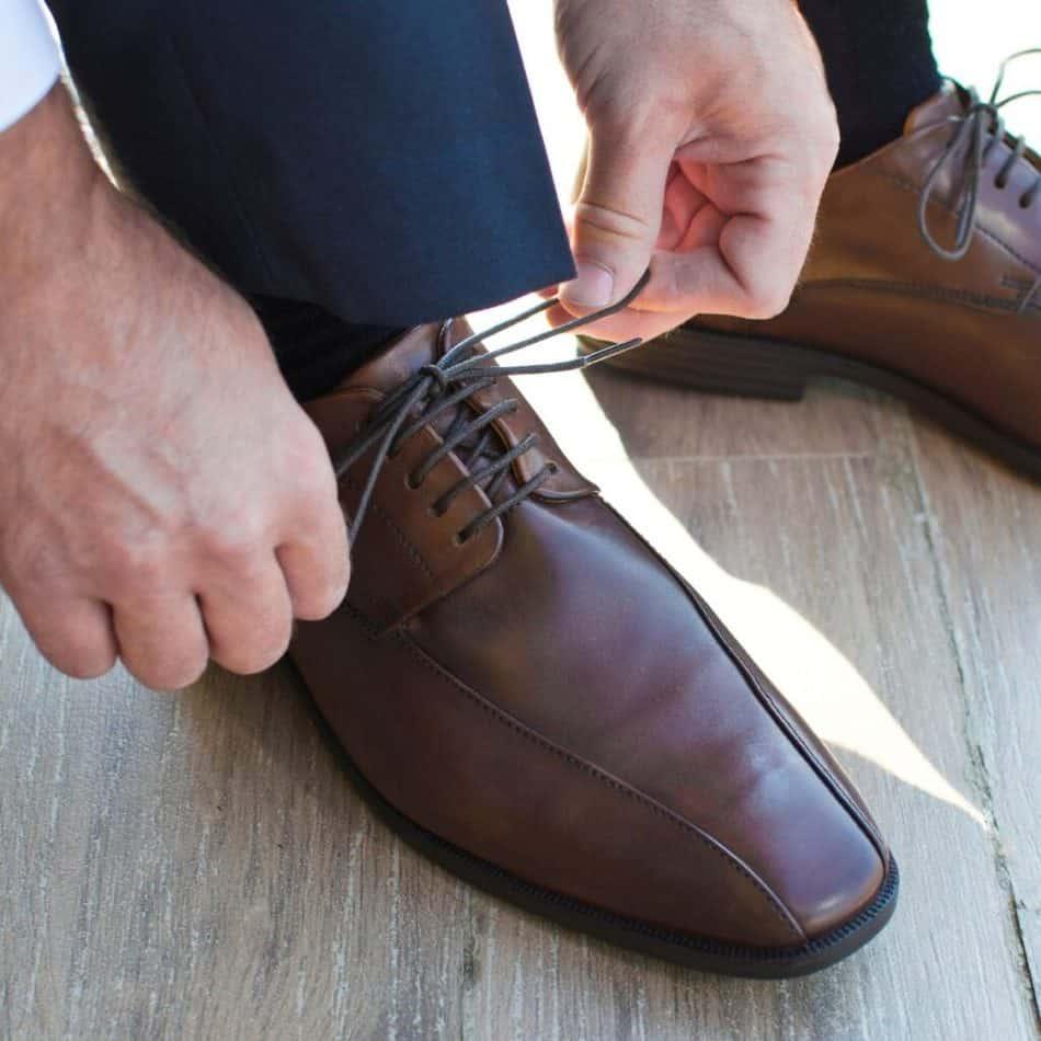 a man tying his brown dress shoe