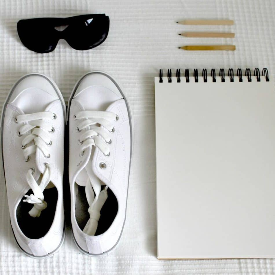 a pair of sneaker next to a notepad and some sunglasses