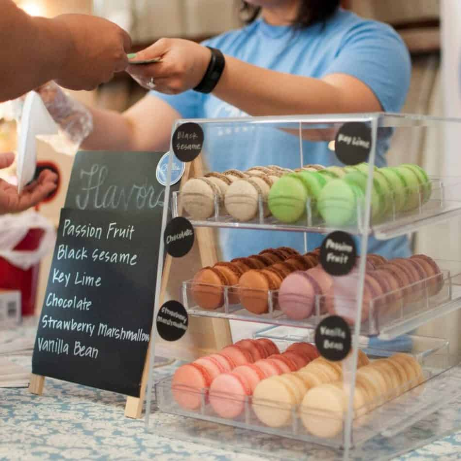 macarons in a display case with a sign to the side