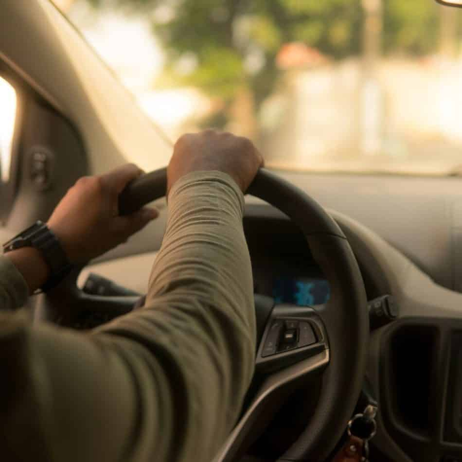 a person driving with hands on the steering wheel