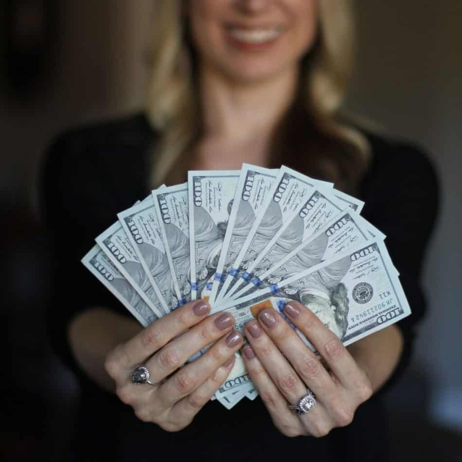 a woman fanning out money in front of the camera