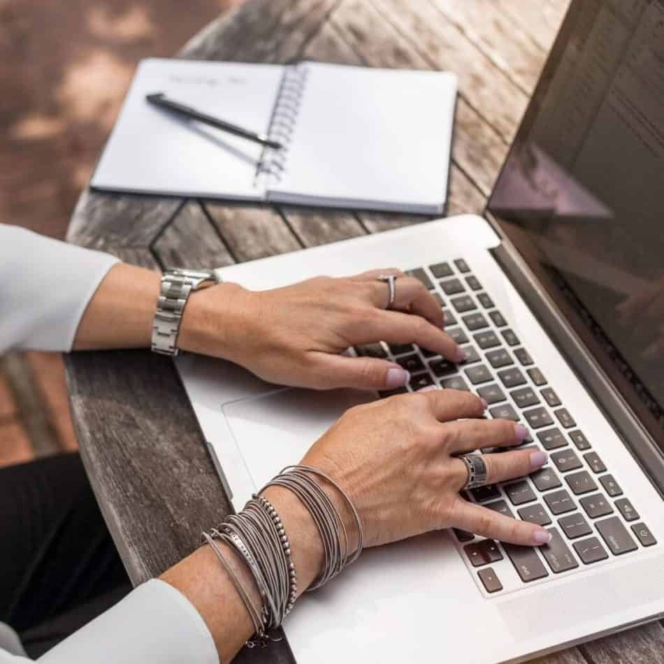 hands typing on a laptop with jewelry on and a notepad