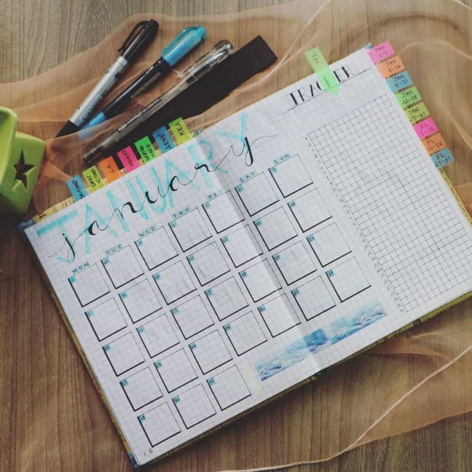 a planner open with pens and highlighters on the side