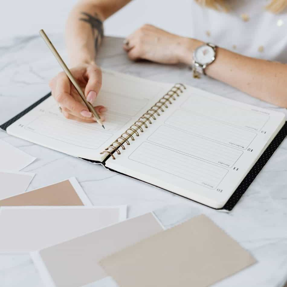 a woman writing in a planner on a desk