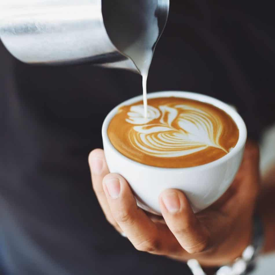 a person pouring a cup of coffee while holding the cup