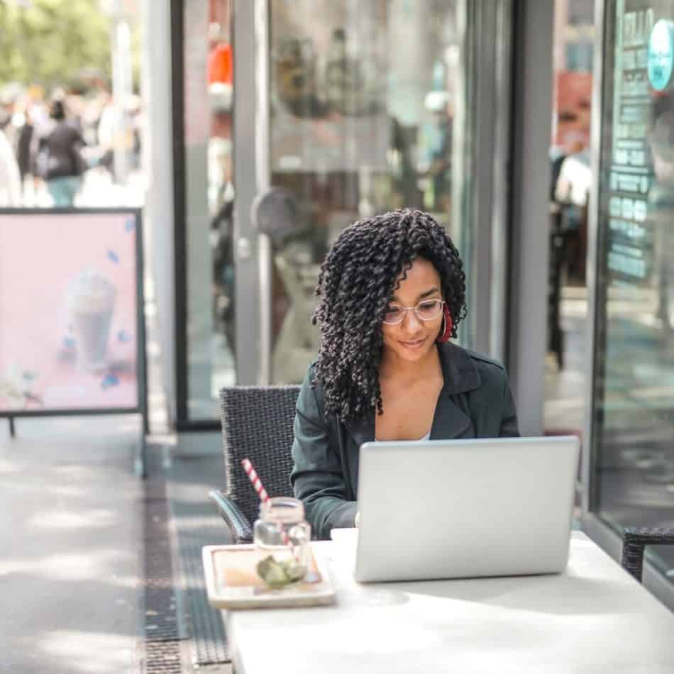 a woman sitting in front of a laptop at a table outside