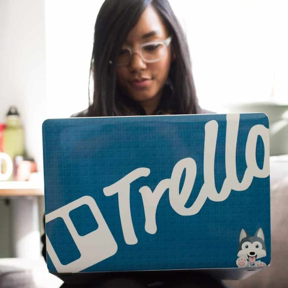 "a woman holding a laptop with a ""Trello"" case"