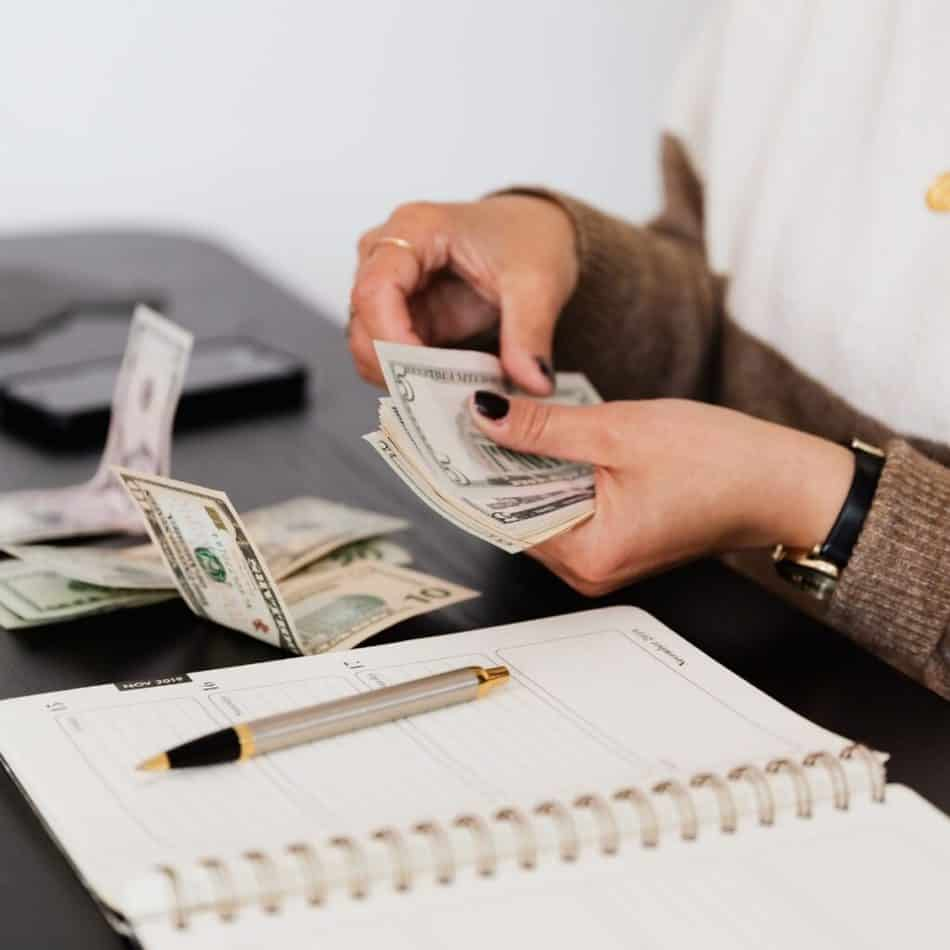 a woman counting money over a notebook on a desk