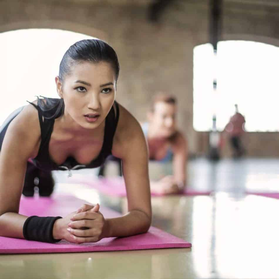 a woman in a plank position in a workout room on a pink yoga mat