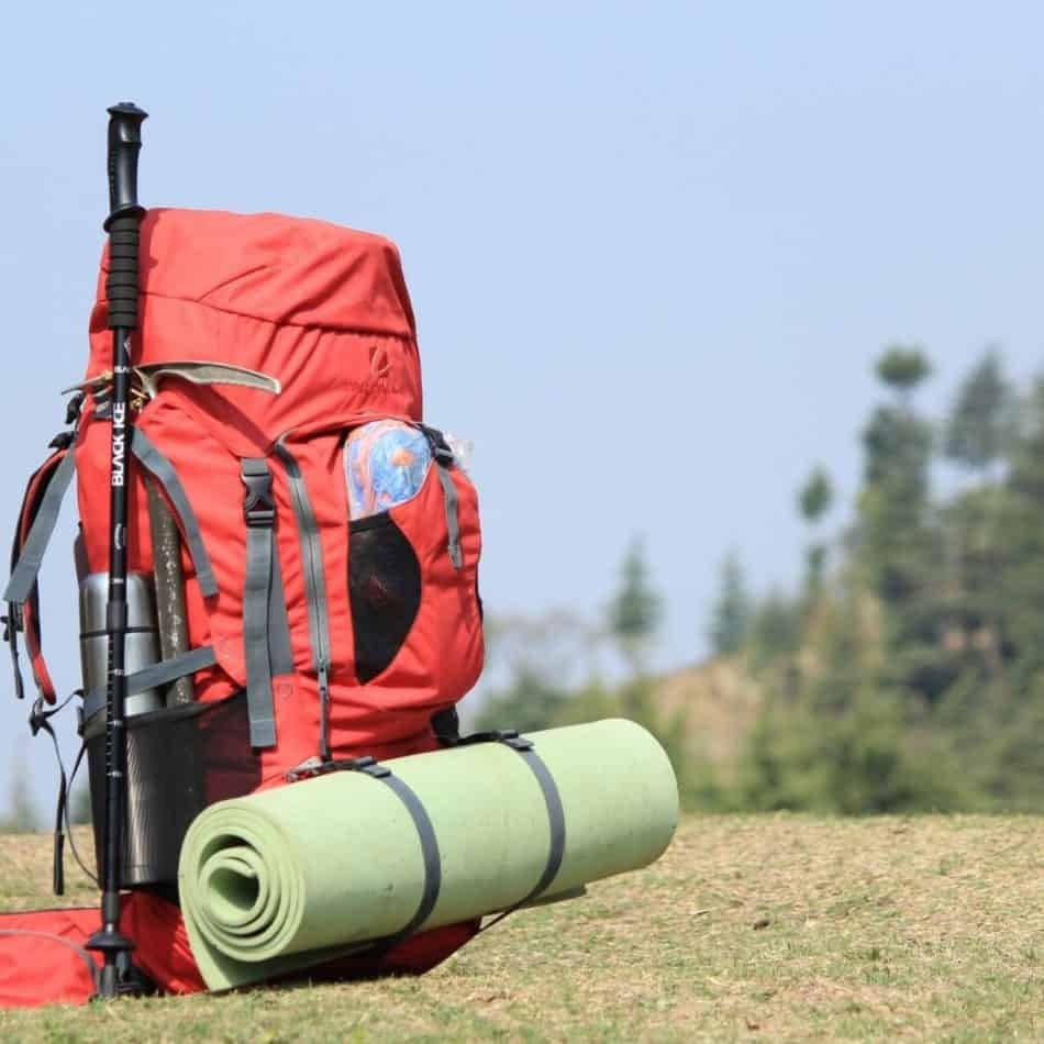 a red backpack with a yoga mat attached