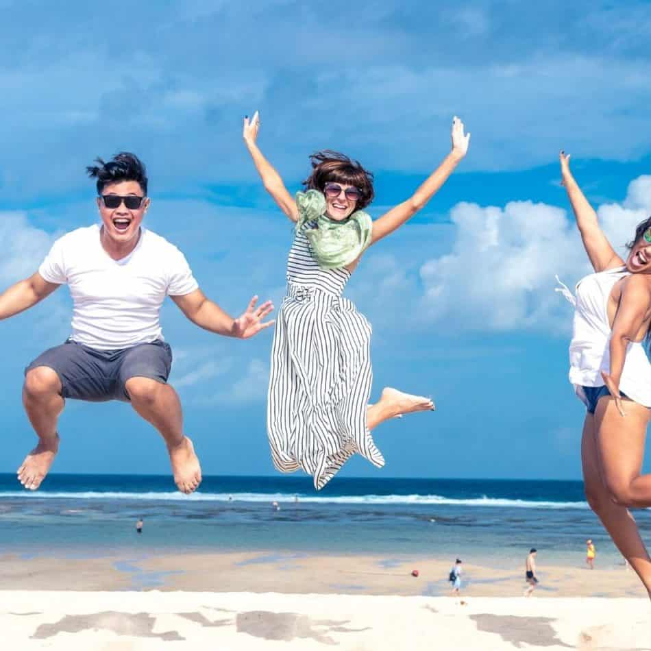 3 people jumping in the air with the ocean in the background